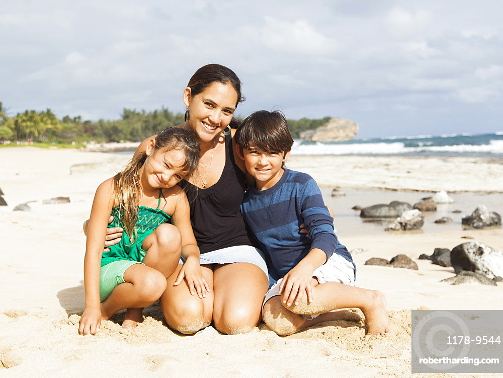 Portrait of girl (6-7) and boy (10-11) sitting on beach with mother, Kauai, Hawaii