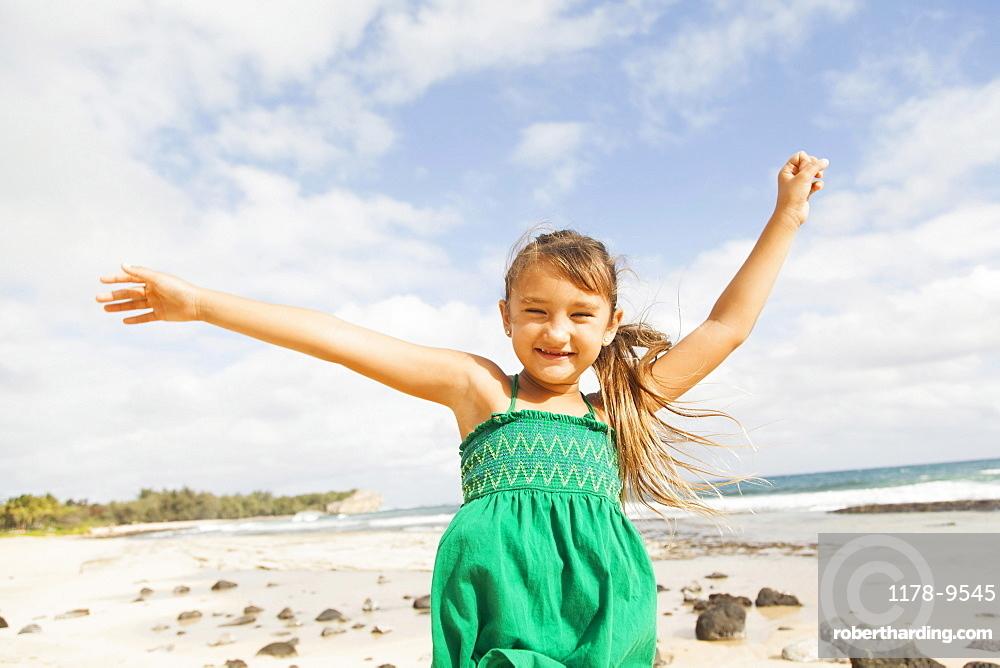 Portrait of girl (6-7) standing on beach with arms raised, Kauai, Hawaii