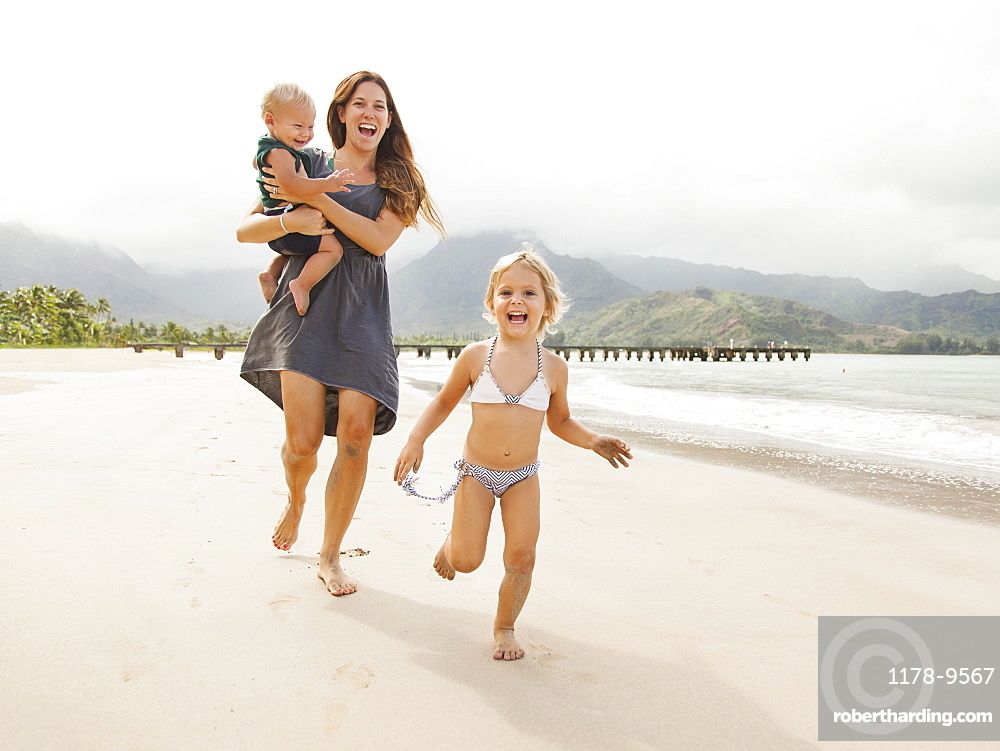 Mother with daughters (6-11 months, 2-3) on beach, Kauai, Hawaii