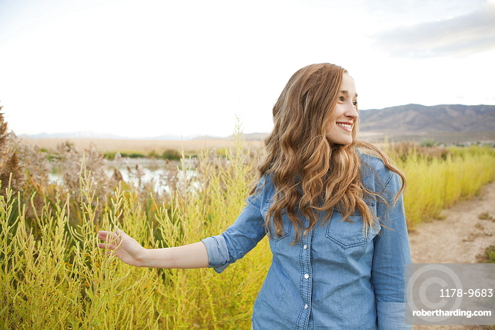 Portrait of young woman on dirt road, Salt Lake City, Utah