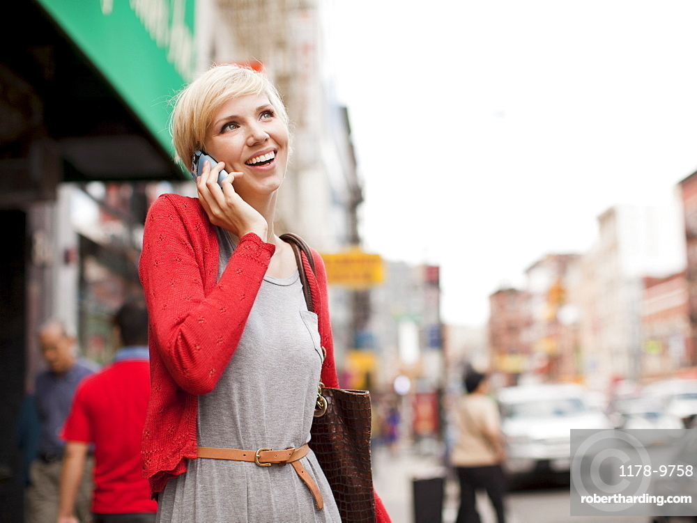 Woman smiling and talking on phone, USA, New York State, New York