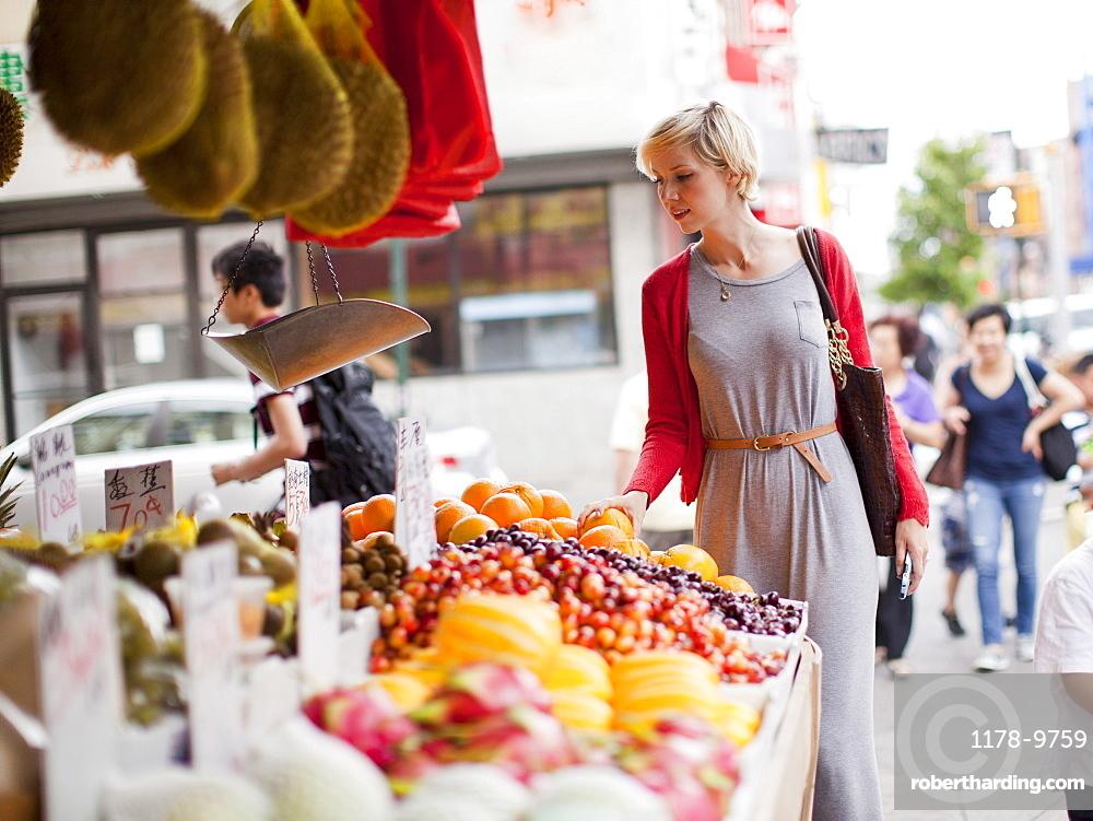 Woman looking at fresh friuts at street market, USA, New York State, New York