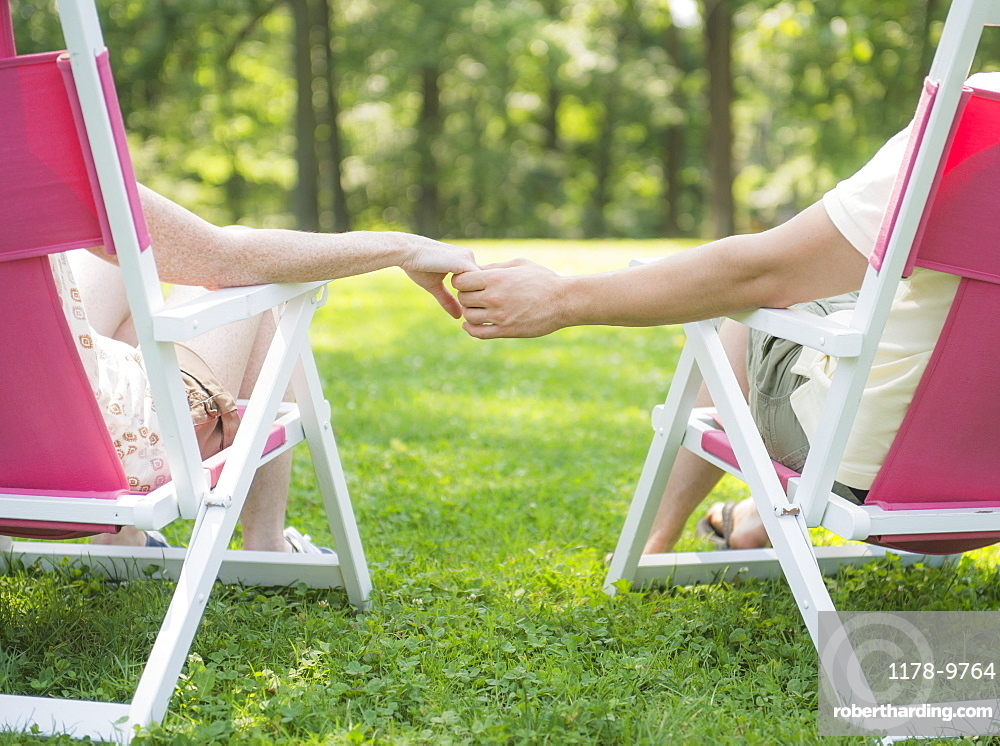 Couple sitting on deck chairs and holding hands, USA, New Jersey, Mendham