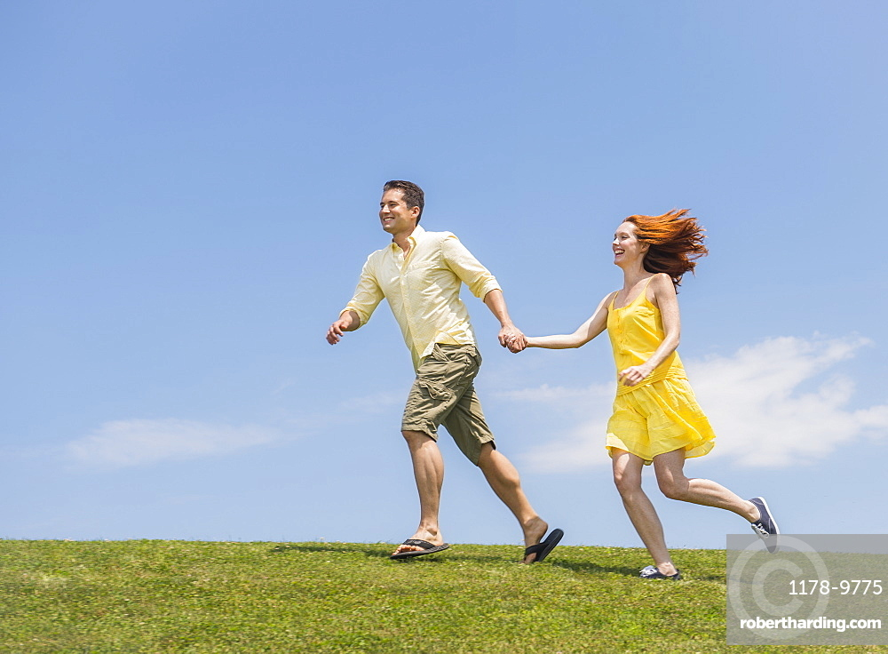 Couple running on meadow, USA, New Jersey, Mendham