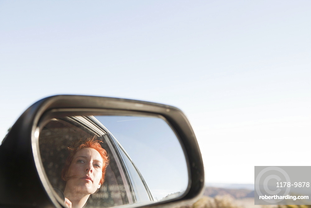 Young woman reflecting in car wing