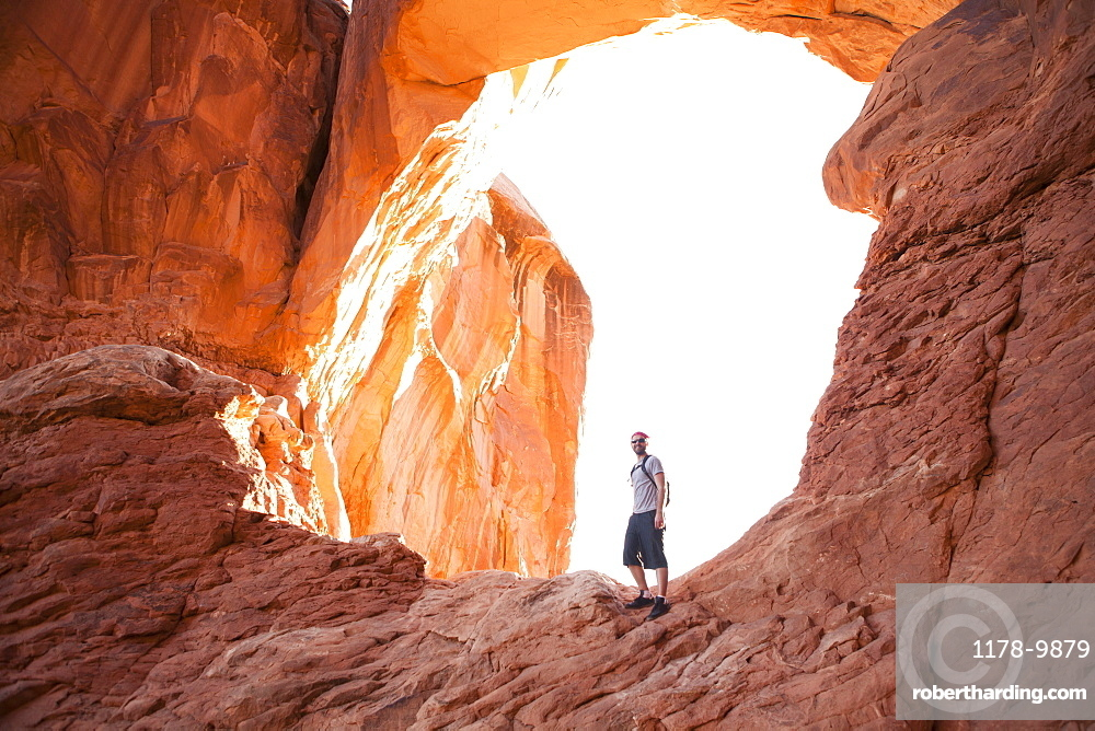 USA, Utah, Moab, Mid adult man posing in front of natural arches, USA, Utah, Moab