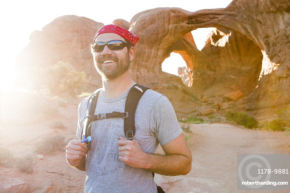 USA, Utah, Moab, Mid adult man posing in front of natural arches, USA, Utah, Moab