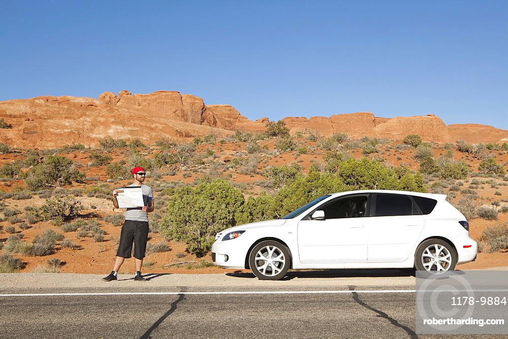 USA, Utah, Moab, Man standing beside car reading map, USA, Utah, Moab