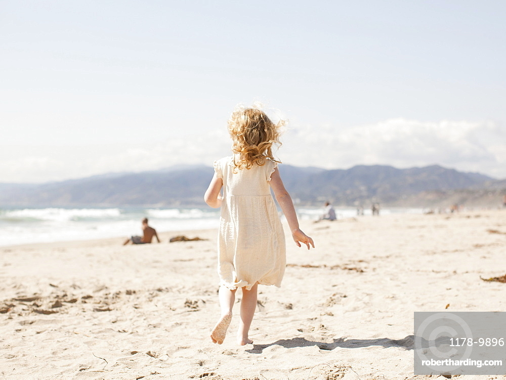 USA, California, Los Angeles, Happy young girl (4-5) running on beach, USA, California, Los Angeles