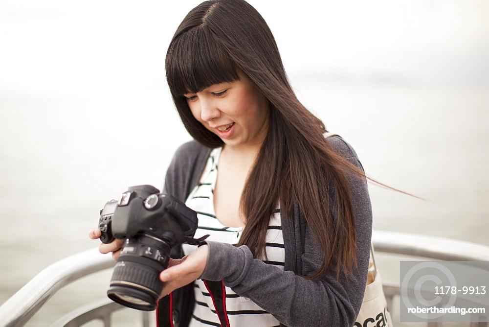 Young woman checking photos in camera