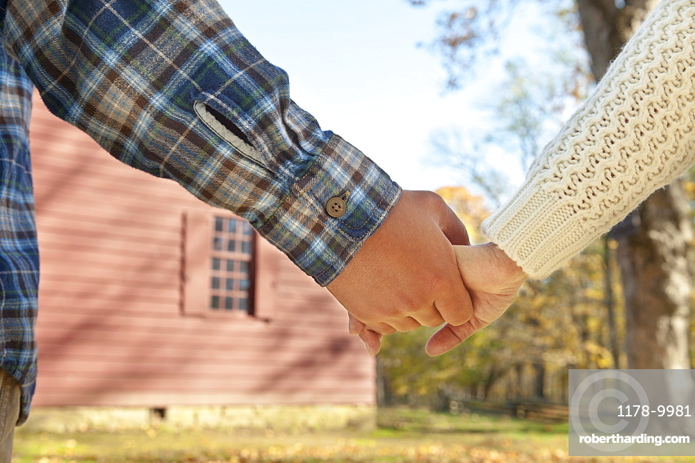 Close-up of couple holding hands in front of cottage house