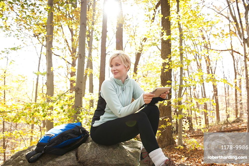 Female hiker using digital tablet in forest