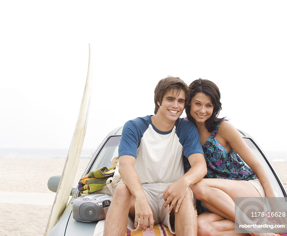 Couple sitting on hood of car at beach