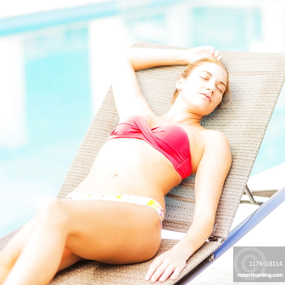 Woman lying on next to swimming pool