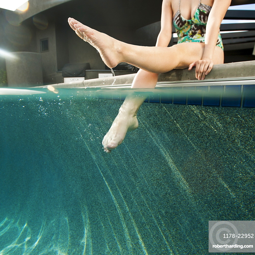 Young attractive woman sitting on edge of swimming pool