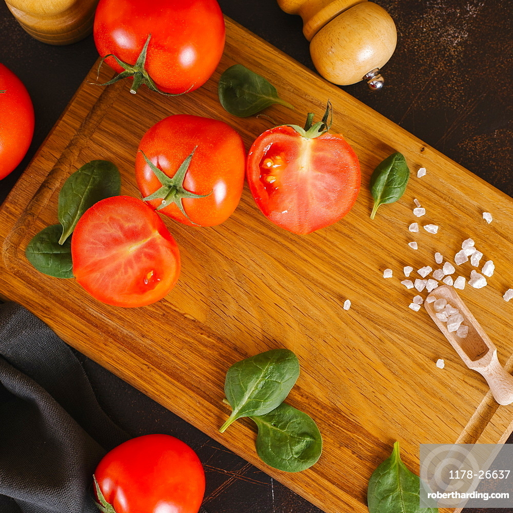 Tomatoes, basil and salt on wooden cutting board
