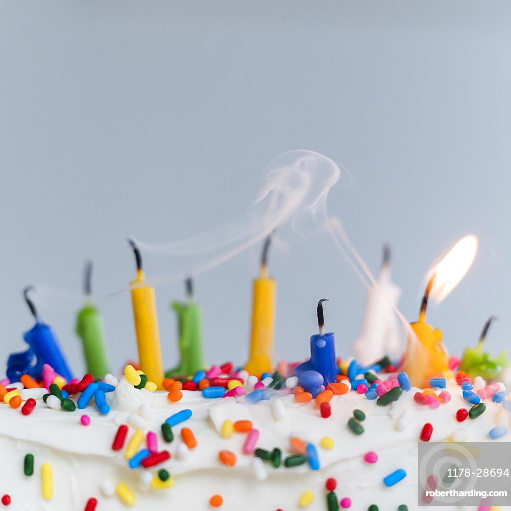 Extinguished birthday candles on cake - one still burning