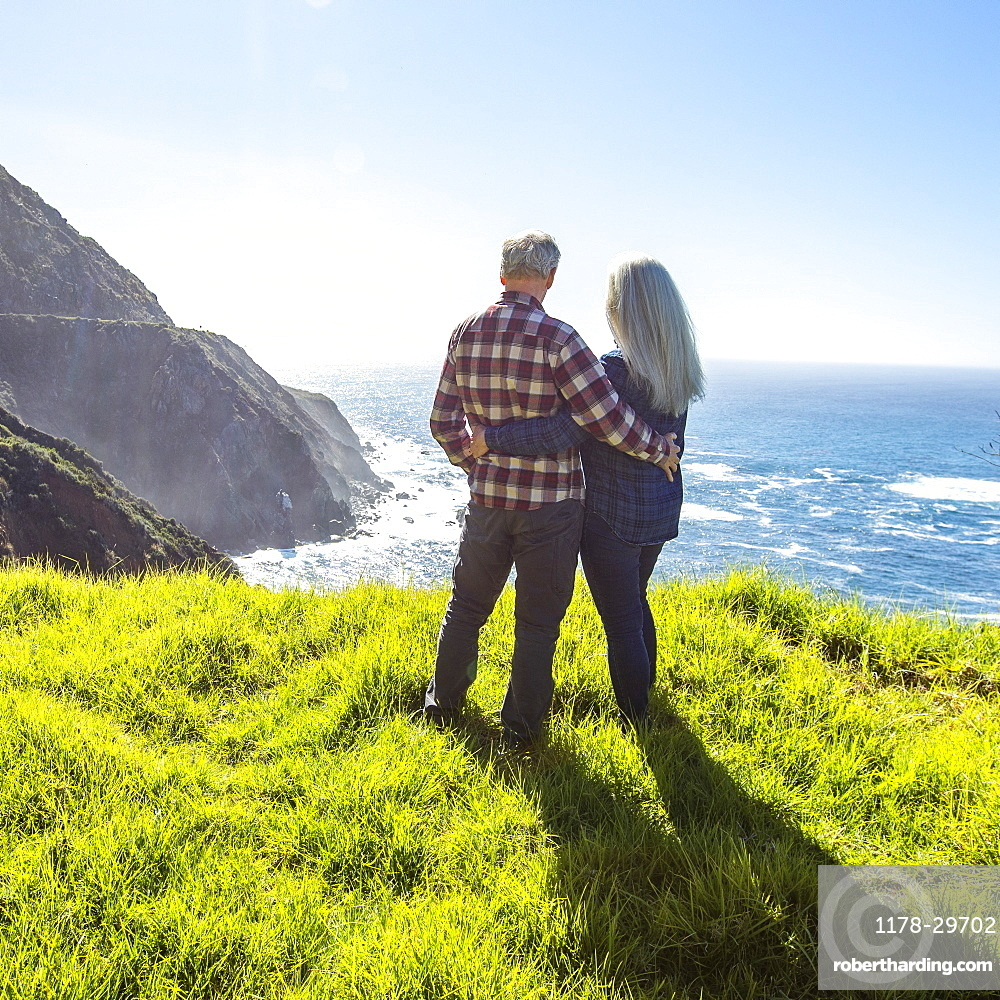 USA, California, Big Sur, Elderly couple watching ocean from grassy cliff