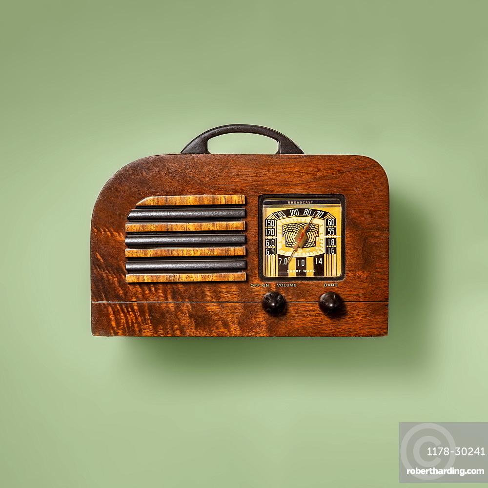 Retro wooden radio on green background