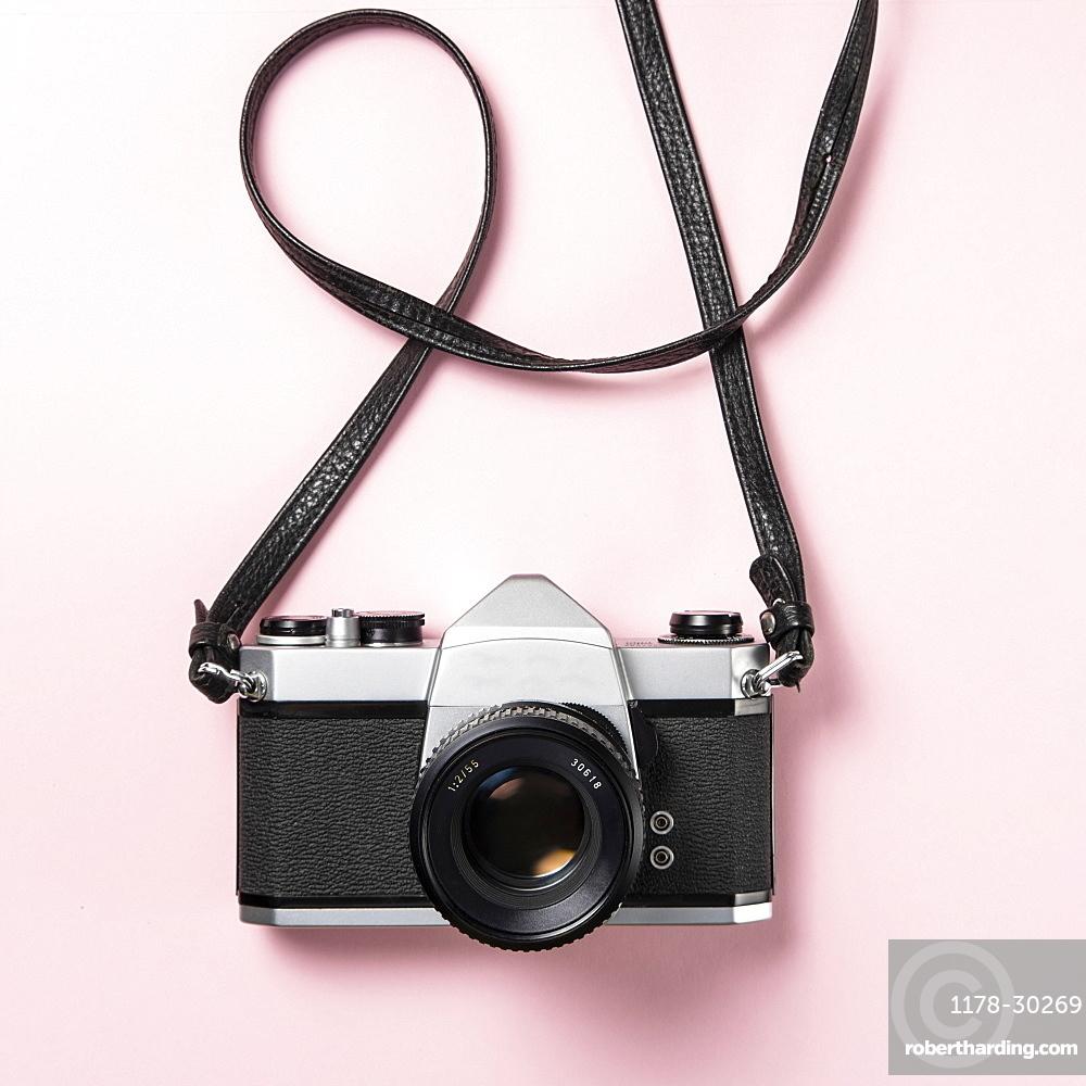 Vintage SLR camera on pink background