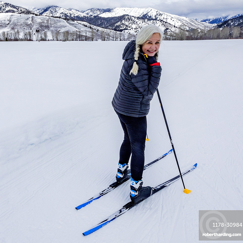 United States, Idaho, sun valley, Portrait of senior woman cross - country skiing on groomed trails