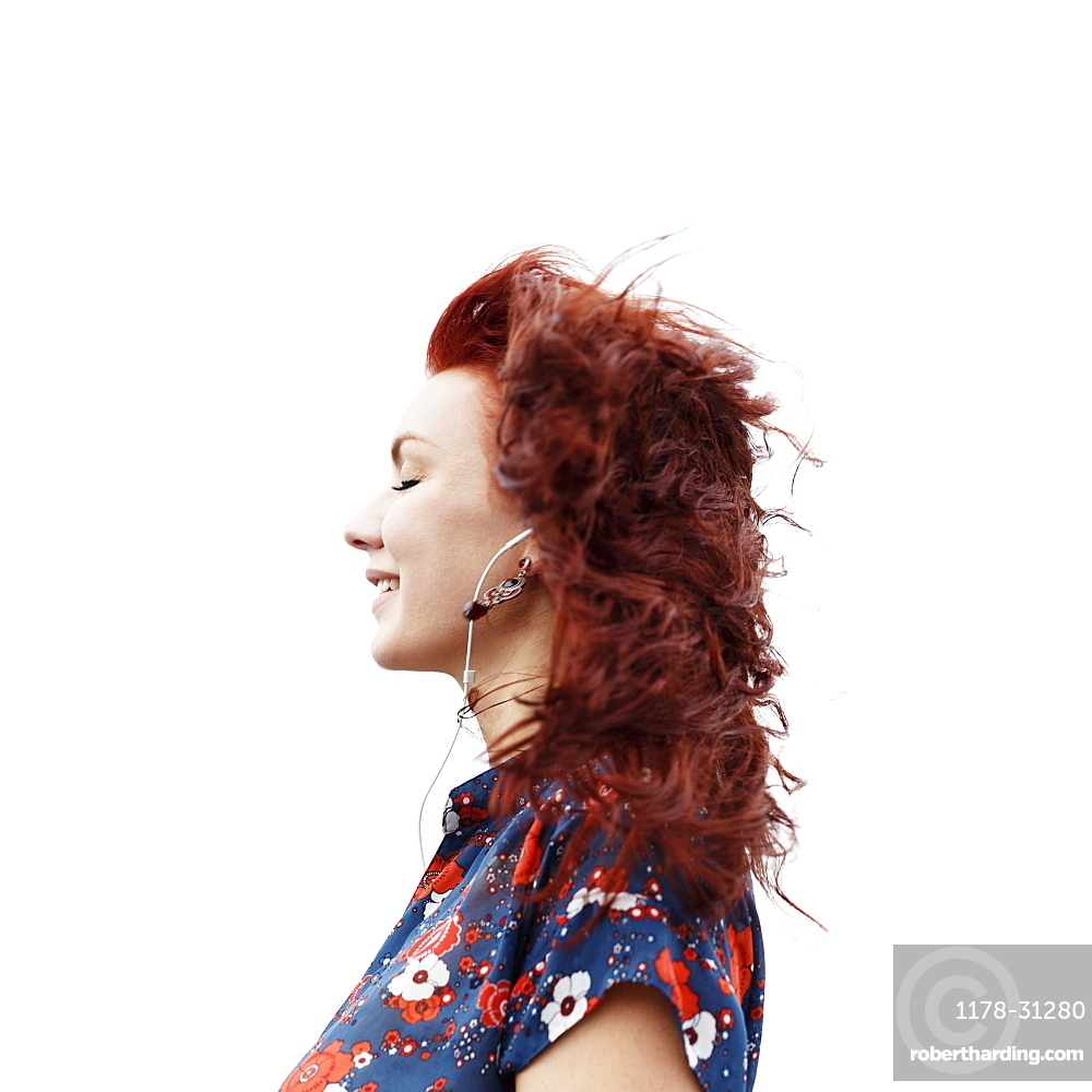 Profile of young woman with long red hair, wearing earphones