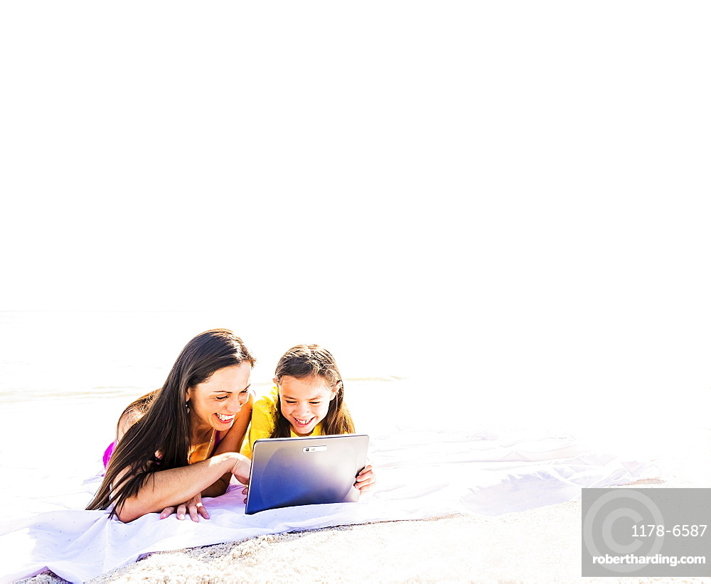 Girl (6-7) lying on beach with her mom and using tablet pc, Jupiter, Florida
