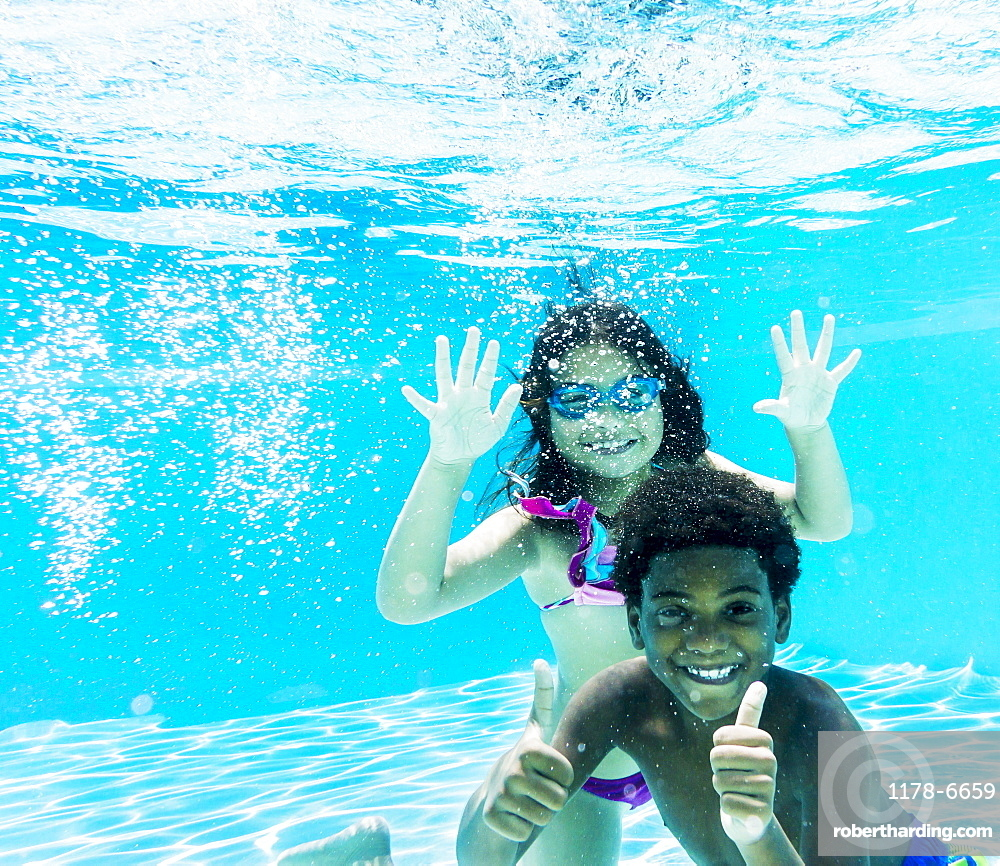 Girl and boy ( 6-7, 8-9) swimming