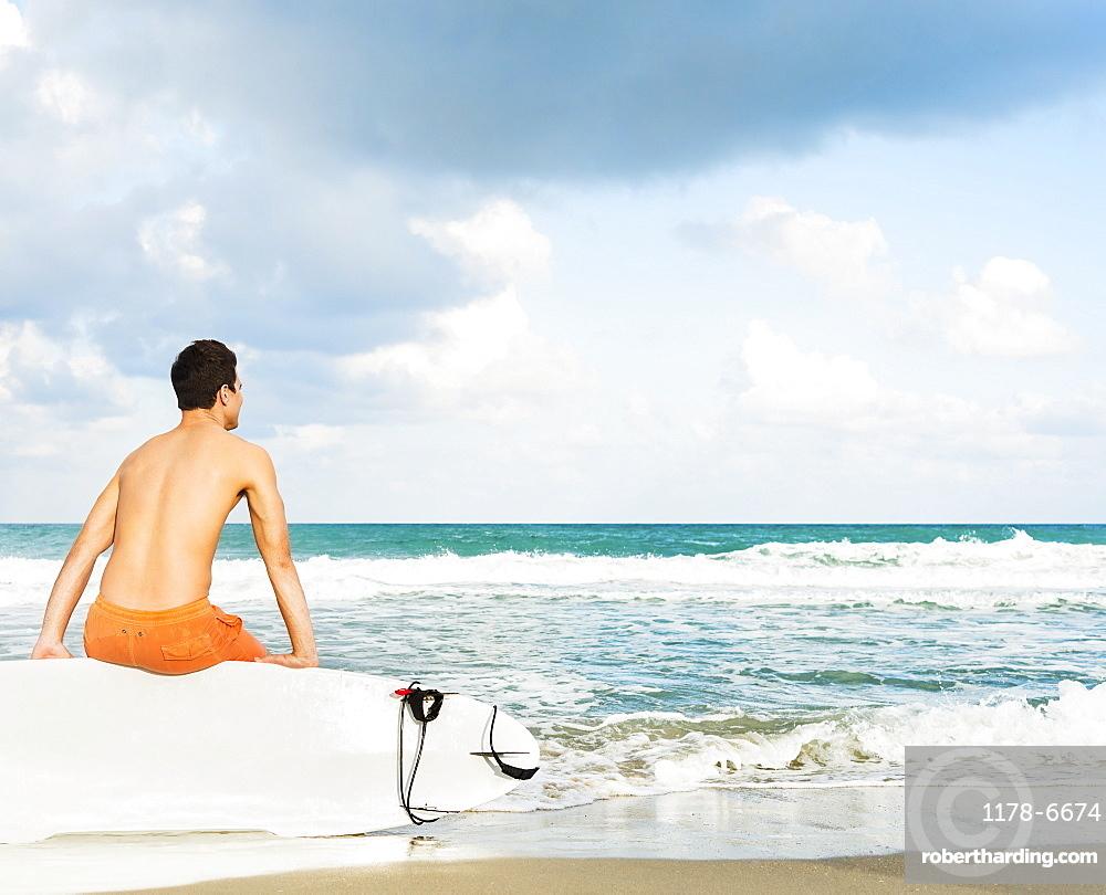 Young man sitting on surfboard, Jupiter, Florida, USA