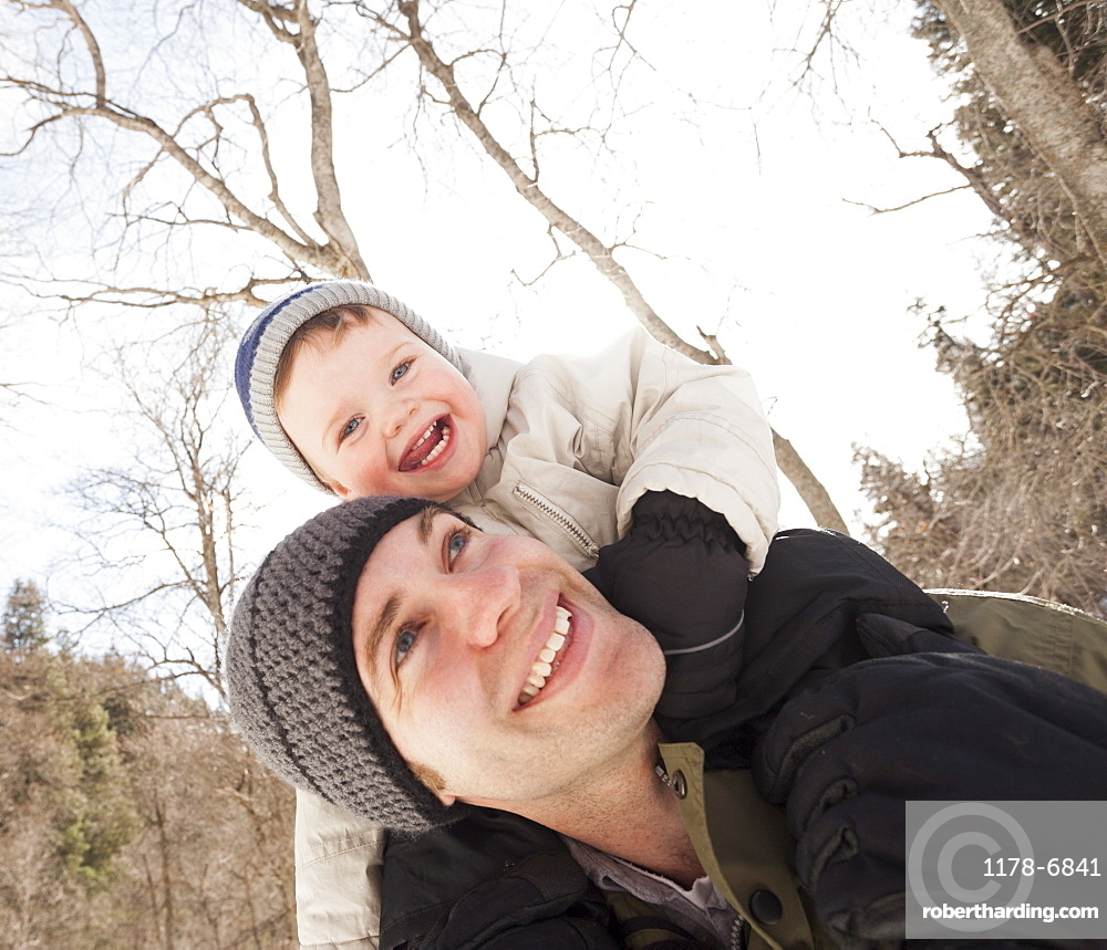 Young man carrying his son (12-17 months) on shoulders, USA, Utah, Highland