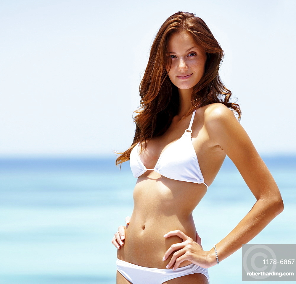 Beach portrait of young woman wearing white bikini