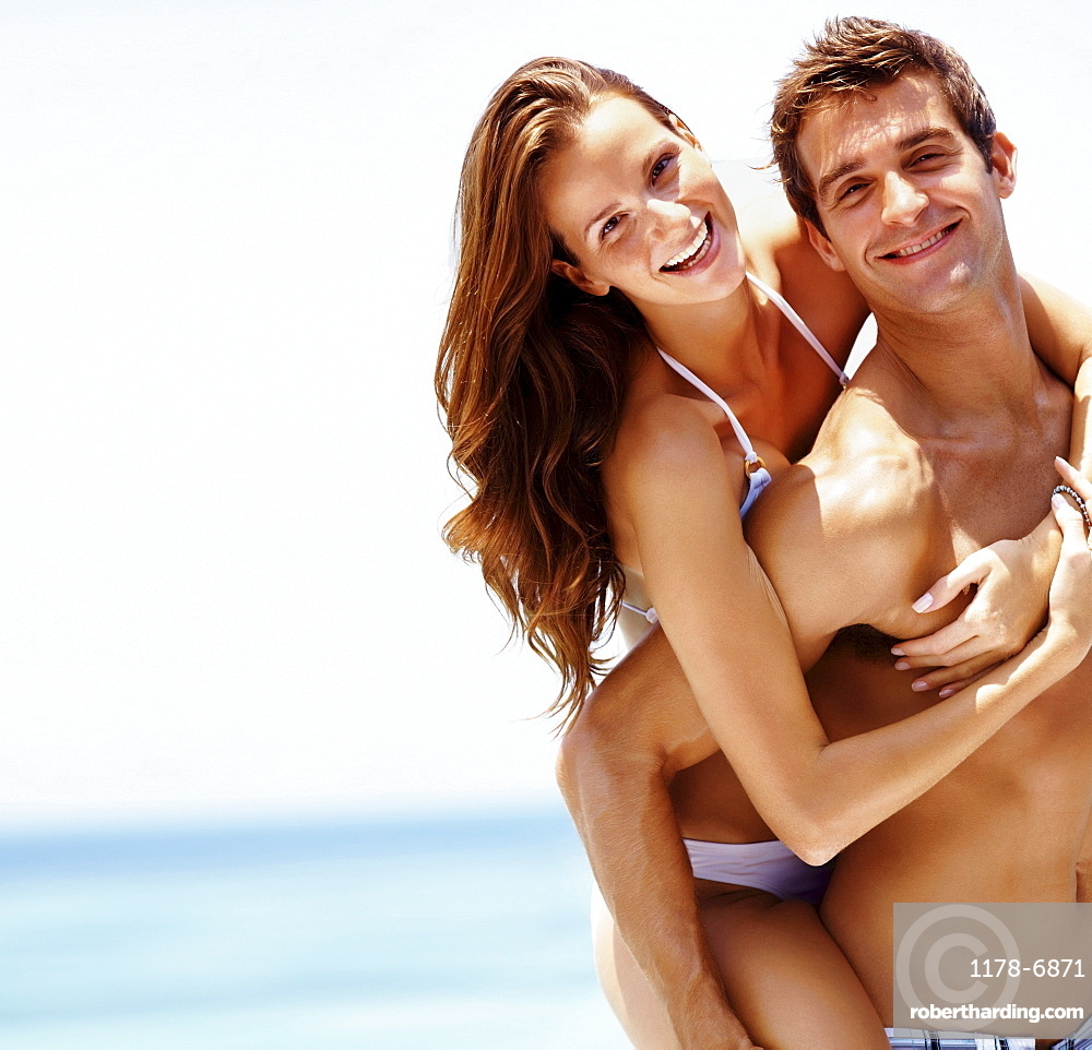 Young attractive couple enjoying summer holiday on beach