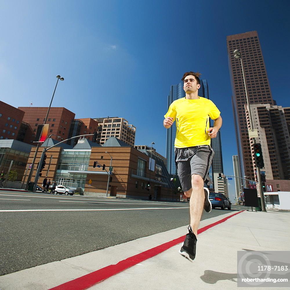 USA, California, Los Angeles, Young man running on city street, USA, California, Los Angeles