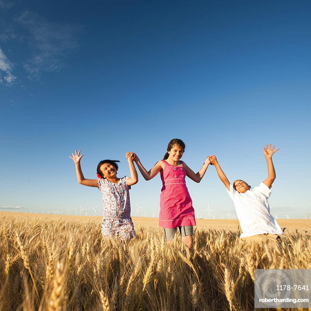 Girls (10-11, 12-13) and boy (8-9) walking though wheat field