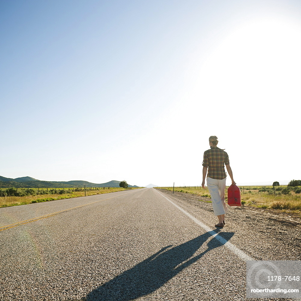 Mid adult woman carrying empty canister along empty road