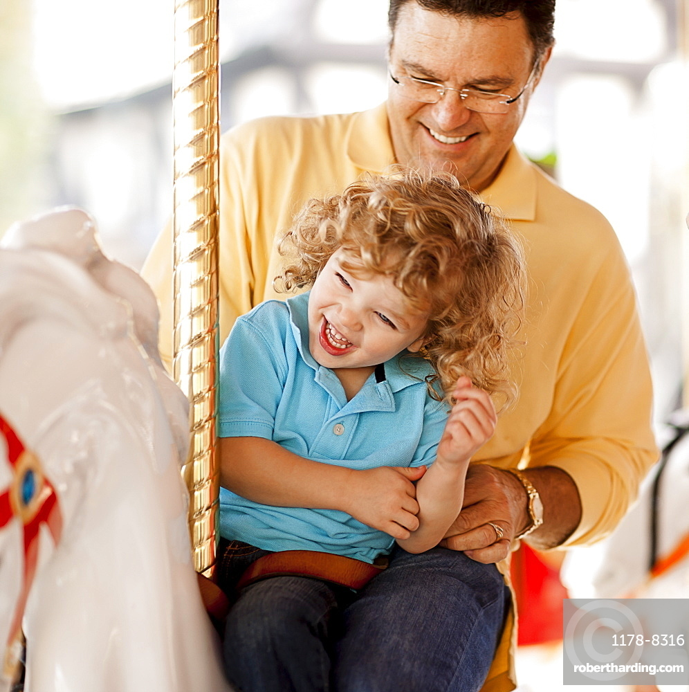 USA, California, Los Angeles, Father with son (4-5) sitting on carousel's horse