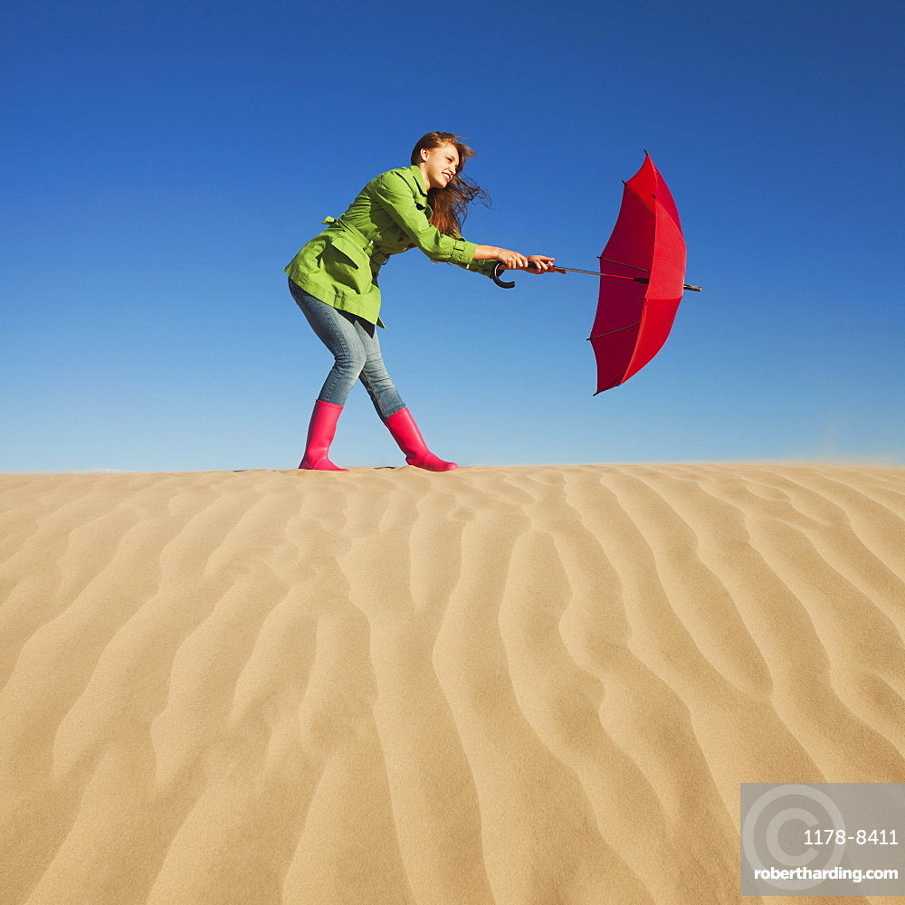 Woman holding red umbrella in the desert