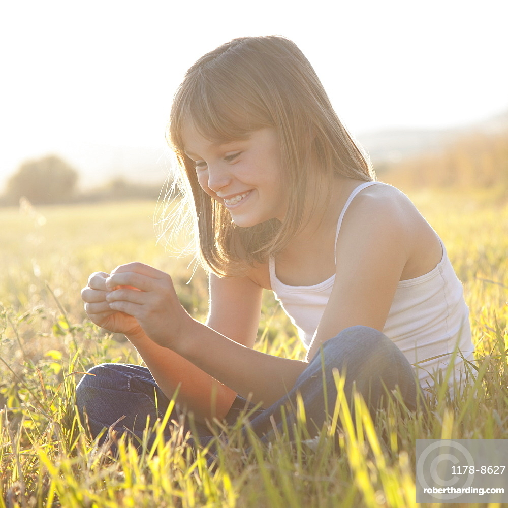 Portrait of young girl sitting in field