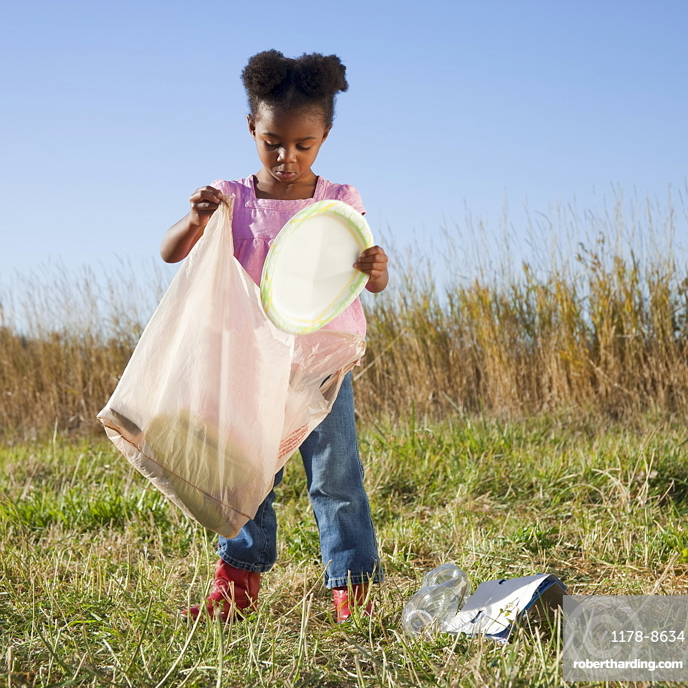 Young girl picking up litter