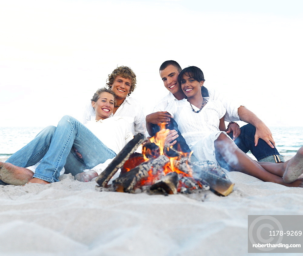 Young couples hugging by campfire on beach