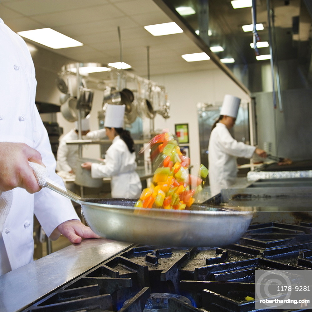 Chef tossing food in skillet