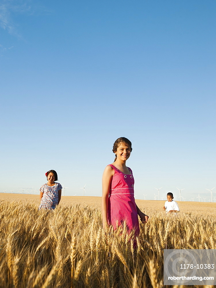Girls (10-11, 12-13) and boy (8-9) standing in wheat field