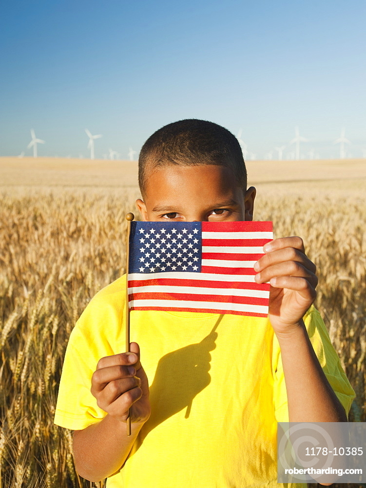 Boy (8-9) holding a small American flag in wheat field