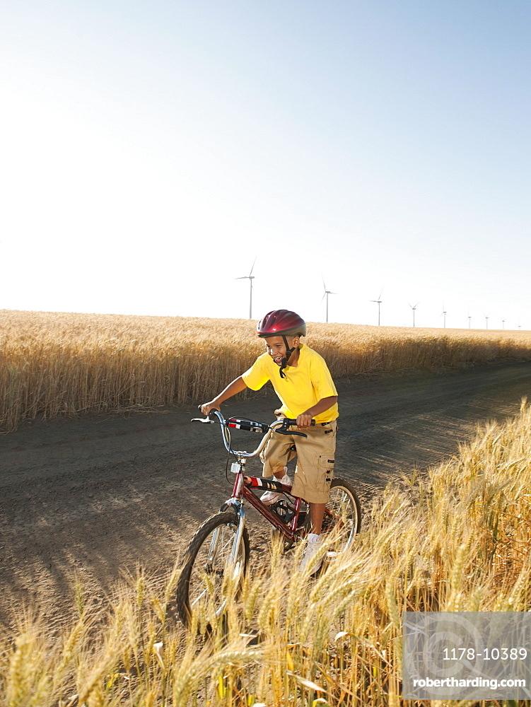 Boy (8-9) cycling along dirt road