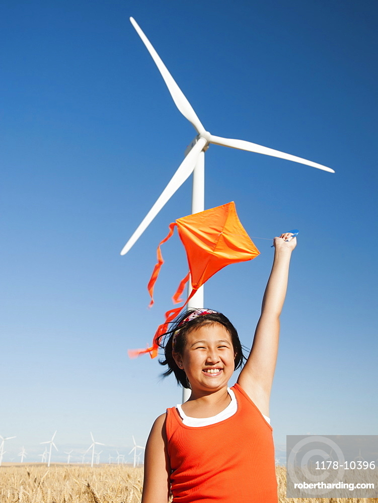 USA, Oregon, Wasco, Girls 10-11) playing with kite in wheat field, wind turbine in background