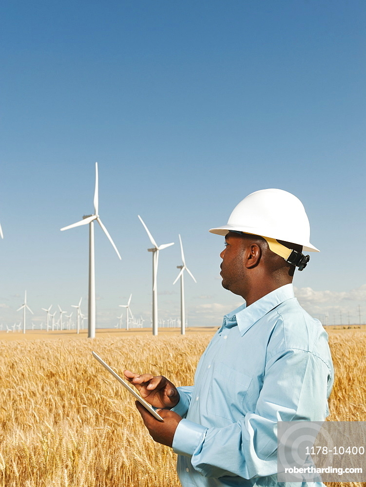 USA, Oregon, Wasco, Engineer standing in wheat field in front of wind turbines, using digital tablet