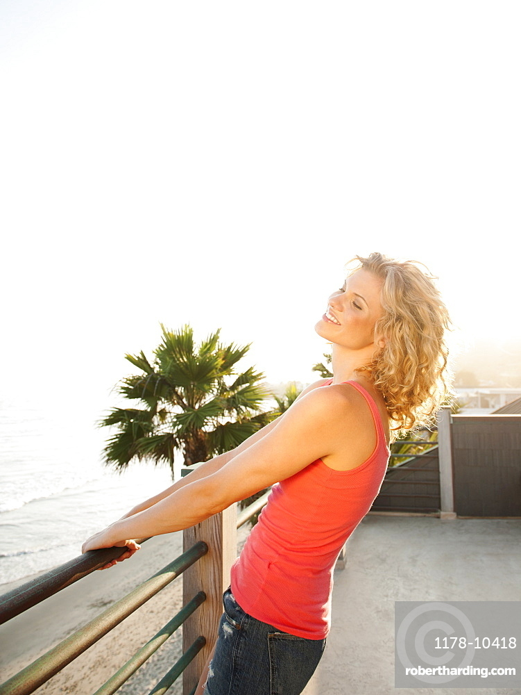 Young attractive woman relaxing on terrace overlooking sea