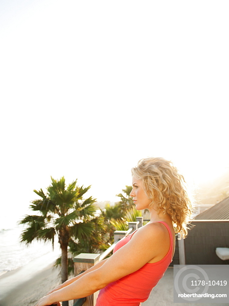 Young attractive woman contemplating seascape from terrace