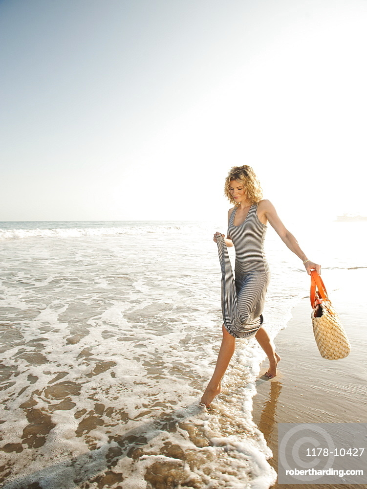 Attractive young woman walking on sandy beach