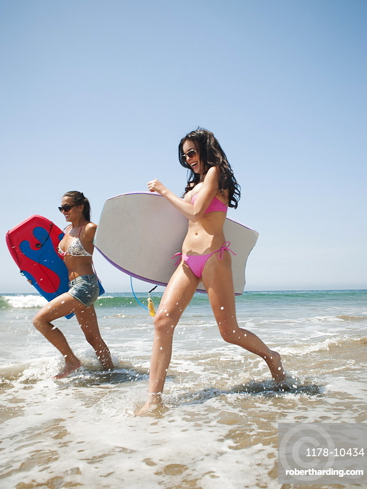 Two young attractive women running into water with swimming boards